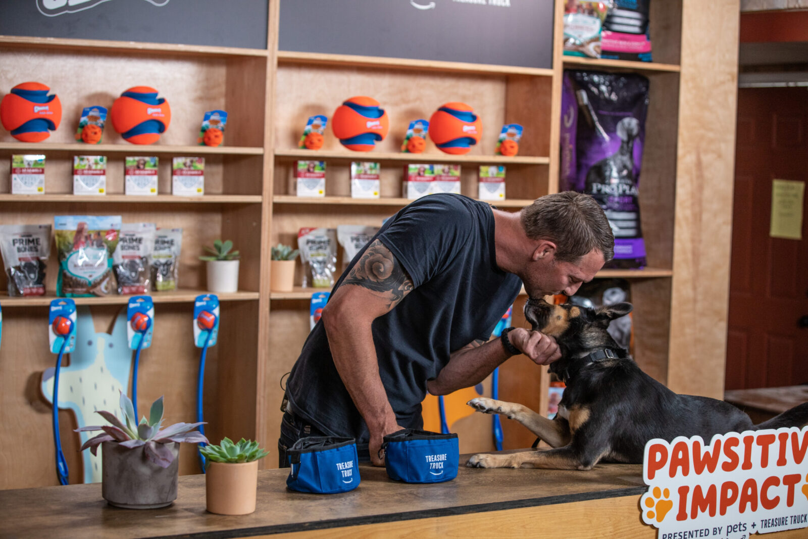 Brandon McMillan and his dog in front of the pawsitive impact experiential design