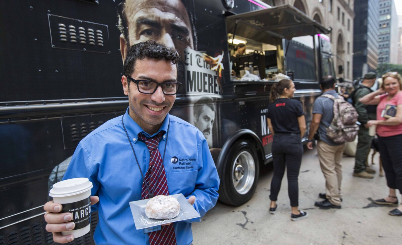 customer posing in front of narcos food truck