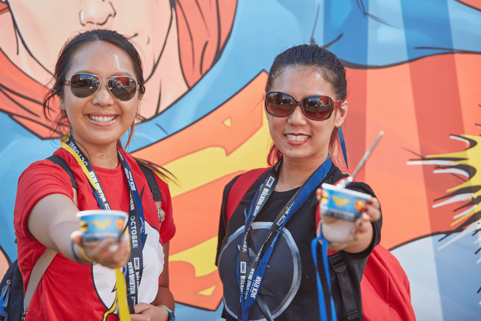 customers posing with superhero ice cream at convention booths